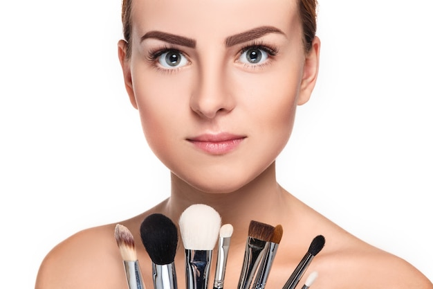 Красивые женские глаза с макияжем и кистью на белом