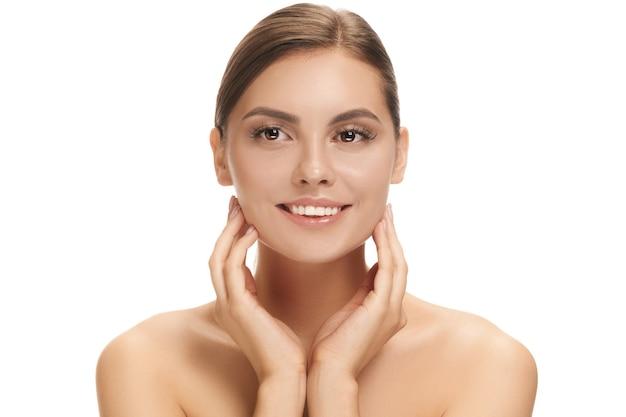 Il bel volto femminile. la pelle perfetta e pulita del viso su bianco. la bellezza, la cura, la pelle, il trattamento, la salute, la spa, il concetto cosmetico