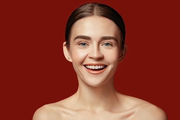 Un bel volto femminile. pelle perfetta e pulita di giovane donna caucasica su sfondo rosso studio.