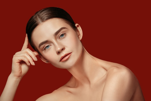 A beautiful female face. perfect and clean skin of young caucasian woman on red studio.