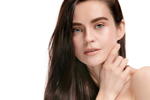 Un bel volto femminile. pelle perfetta e pulita di giovane donna caucasica su studio bianco.