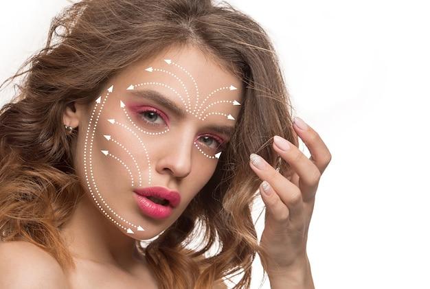 Красивое женское лицо с ярким макияжем на белом фоне. концепция ухода за телом, косметики, ухода за кожей и лифтинга, коррекционной хирургии, красоты, идеальной кожи. красочный флаер для вашей рекламы. против старения.