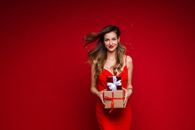 Красивая фотомодель в красном платье держит много маленьких коробок с подарками и радуется
