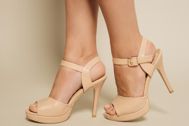 Красивые женские ноги в коричневых босоножках на высоких каблуках