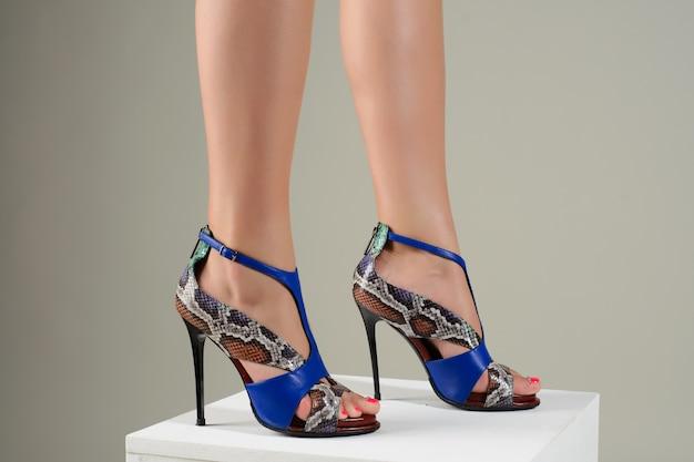 白のスタイリッシュな青いハイヒールのサンダルで美しい女性の足