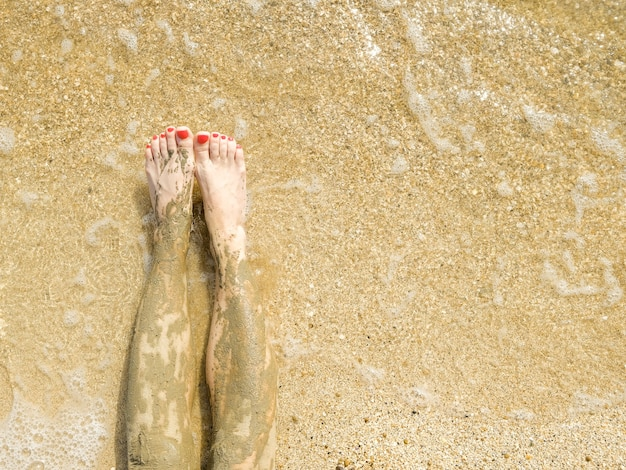 Beautiful female feet smeared with curative mud on the sand of the beach by the water