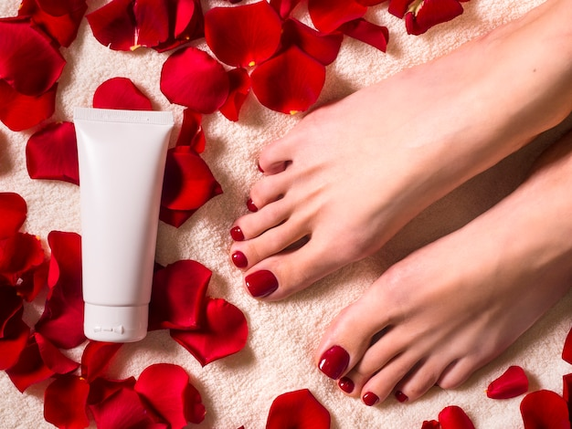 Beautiful female feet with a beautiful pedicure with a tube of cream on a terry towel with rose petals. spa and skin care concept.