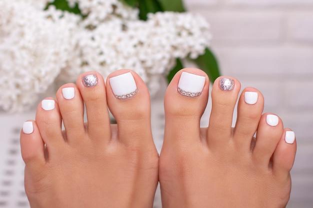 Красивые женские ножки с модным маникюром на ногтях белый и серебристый гель-лак