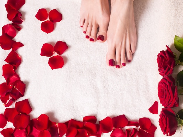 Beautiful female feet with a red pedicure in a bath with salt and rose petals. spa and skin care concept.