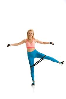 Красивый женский фитнес-тренер, практикующий на белом студийном фоне, показаны упражнения