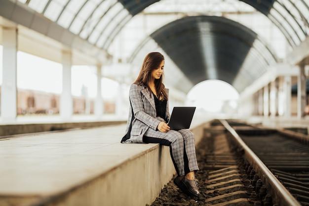 기차를 기다리는 동안 거리 작업을 위해 노트북을 사용하는 아름다운 여성 프리랜서.