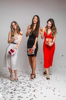 샴페인과 흰색 벽에 고립 된 그들 주위에 많은 색종이 드레스에서 아름 다운 여자 친구