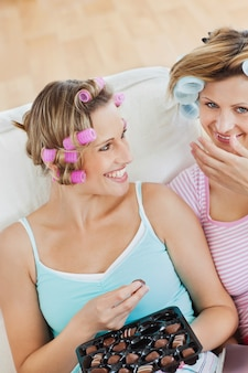 Beautiful female friends with hair rollers eating chocolate at home