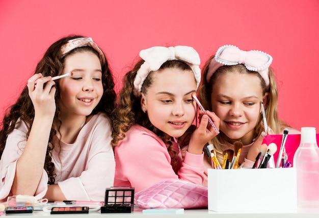 美しい女性。友情と姉妹関係。家族の絆の時間。子供の頃の幸せ。レトロな子供たちは化粧をします。子供のためのスキンケア化粧品。美しさとファッション。美容院で3人の幸せな女の子。