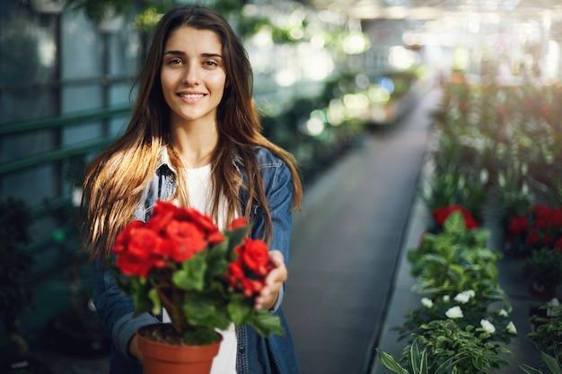 카메라 미소를보고 꽃을 돌보는 아름 다운 여성 정원사.