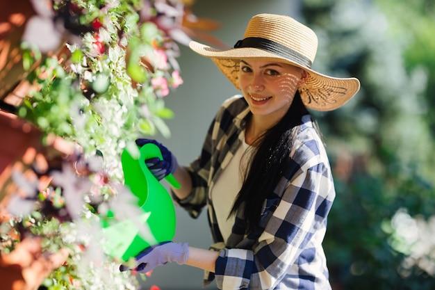 더운 여름 날에 정원에서 식물을 급수하는 아름 다운 여성 정원사. 원예 개념.