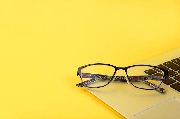 Красивые женские очки лежат на ноутбуке с желтым фоном. бизнес-идея. скопируйте пространство.