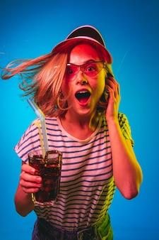 Beautiful female half-length portrait isolated on blue neon lights studio