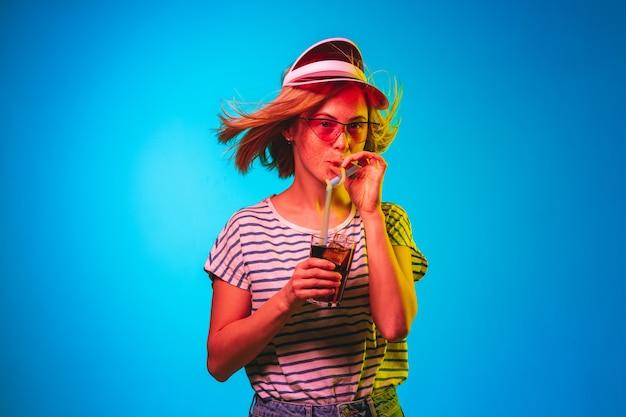 블루 네온 조명 스튜디오에 고립 된 아름 다운 여성 절반 길이 초상화