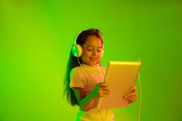 네온 불빛에 녹색 backgroud에 고립 된 아름 다운 여성 절반 길이 초상화. 감정적 인 소녀. 인간의 감정, 표정 개념. 트렌디 한 색상. 게임, 동영상 블로그, 셀카에 태블릿 사용.