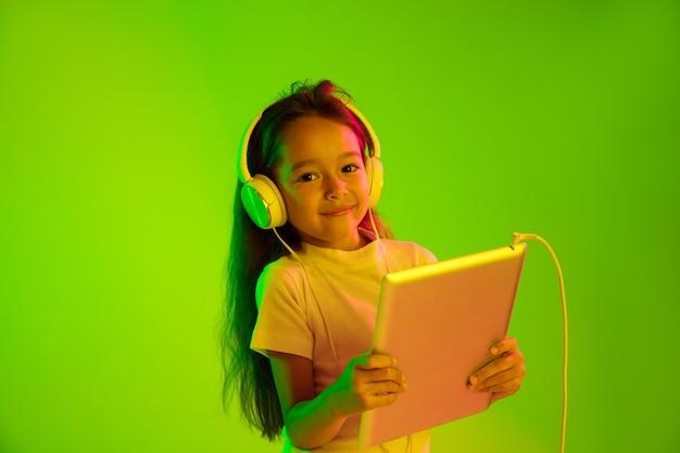 ネオンの光の中で緑の背景に分離された美しい女性の半分の長さの肖像画。若い感情的な女の子。人間の感情、顔の表情の概念。トレンディな色。ゲーム、vlog、セルフィーにタブレットを使用する。