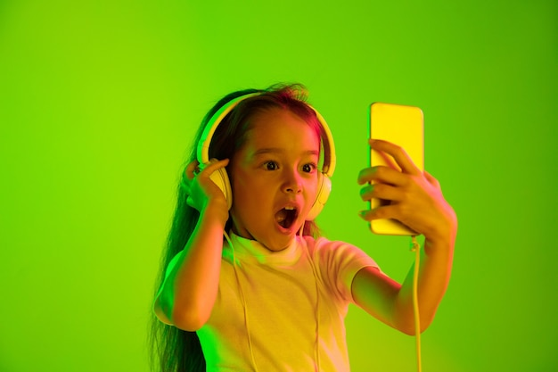 네온 불빛에 녹색 backgroud에 고립 된 아름 다운 여성 절반 길이 초상화. 감정적 인 소녀. 인간의 감정, 표정 개념. 동영상 블로그, 셀카, 채팅, 게임에 스마트 폰 사용.