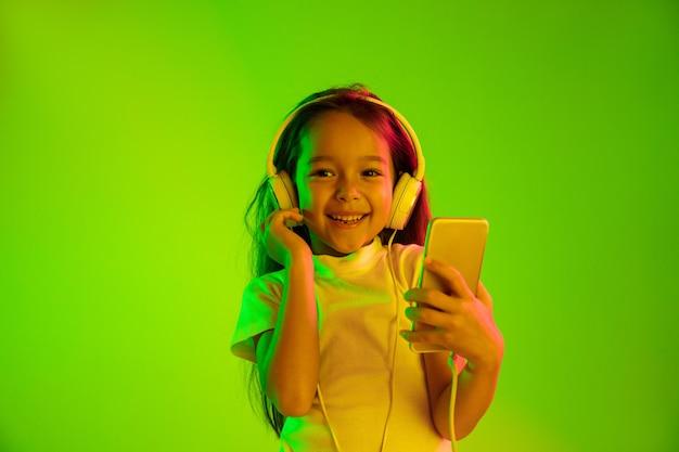 ネオンの光の中で緑の背景に分離された美しい女性の半分の長さの肖像画。若い感情的な女の子。人間の感情、顔の表情の概念。 vlog、selfie、チャット、ゲームにスマートフォンを使用する。