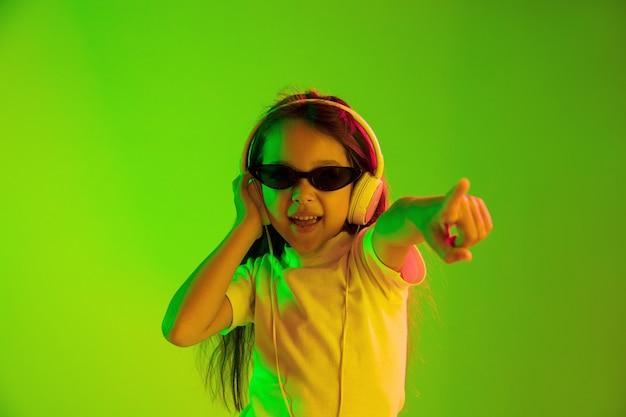 ネオンの光の中で緑の背景に分離された美しい女性の半分の長さの肖像画。若い感情的な十代の少女。人間の感情、顔の表情の概念。サングラスで踊り、上向き。