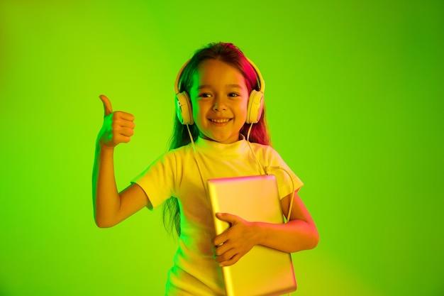 네온 불빛에 녹색 backgroud에 고립 된 아름 다운 여성 절반 길이 초상화. 젊은 감정적 인 십 대 소녀. 인간의 감정, 표정 개념. 트렌디 한 색상. 태블릿을 들고 웃 고.