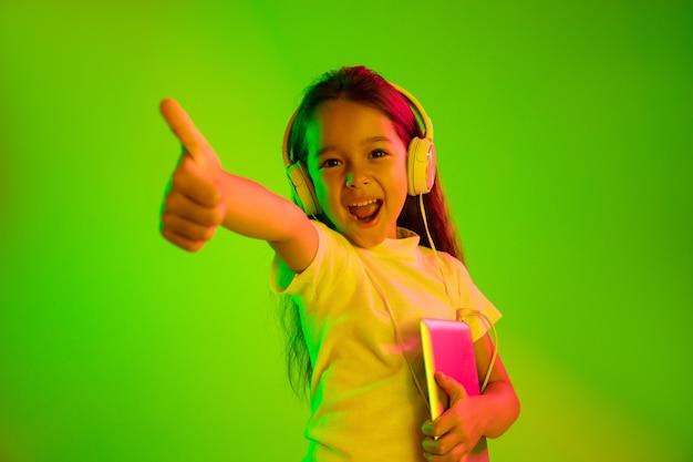 ネオンの光の中で緑の背景に分離された美しい女性の半分の長さの肖像画。若い感情的な十代の少女。人間の感情、顔の表情の概念。トレンディな色。タブレットを持って笑顔。