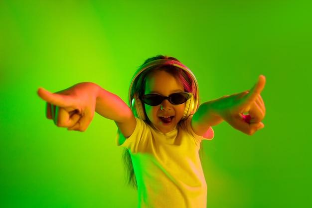 ネオンの光の中で緑の背景に分離された美しい女性の半分の長さの肖像画。サングラスをかけた若い感情的な十代の少女。人間の感情、顔の表情の概念。トレンディな色。踊って、笑って。