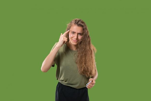 グリーンスタジオに分離された美しい女性の半身像。感情的な若い女性