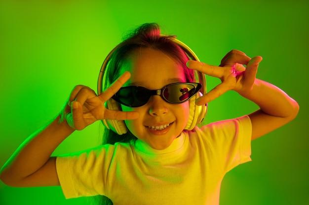 네온 불빛에 녹색 벽에 고립 된 아름 다운 여성 절반 길이 초상화. 선글라스에 젊은 감정적 인 십 대 소녀. 인간의 감정, 표정 개념. 트렌디 한 색상. 춤추고 웃고.