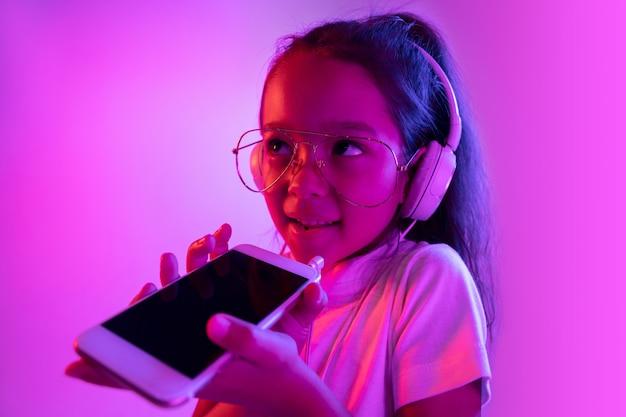 ネオンの光の中で紫色の背景に分離された美しい女性の半分の長さの肖像画。眼鏡の感情的な女の子。人間の感情、顔の表情の概念。音楽を聴いたり、ボイスメッセージを録音したりします。