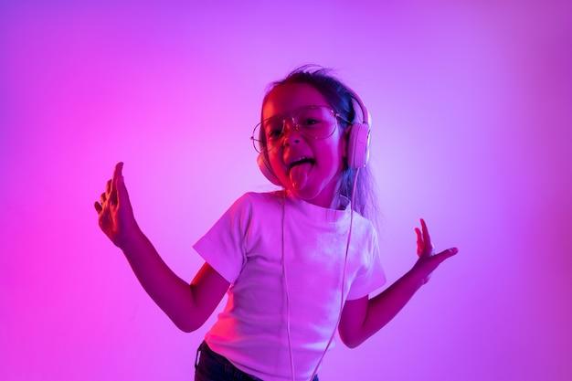 ネオンの光の中で紫色の背景に分離された美しい女性の半分の長さの肖像画。眼鏡の若い感情的な十代の少女。人間の感情、顔の表情の概念。トレンディな色。踊って、笑って。