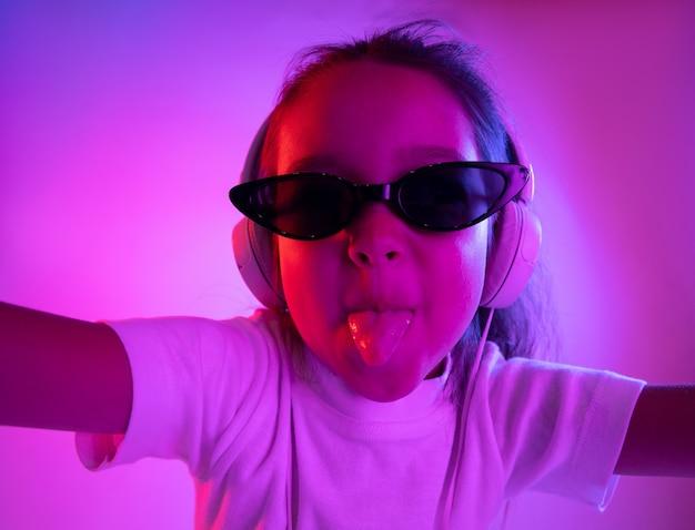 네온 불빛에 보라색 벽에 고립 된 아름 다운 여성 절반 길이 초상화. 선글라스에 젊은 감정적 인 소녀. 인간의 감정, 표정 개념. 트렌디 한 색상.