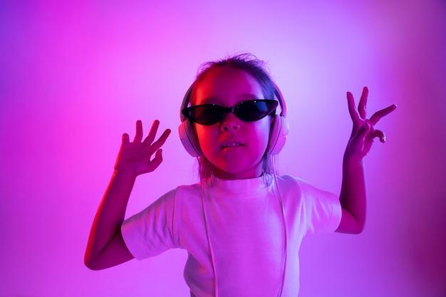 네온 불빛에 보라색 벽에 고립 된 아름 다운 여성 절반 길이 초상화. 선글라스에 젊은 감정적 인 십 대 소녀. 인간의 감정, 표정 개념. 트렌디 한 색상. 춤추고 웃고.
