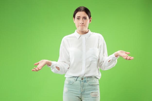유행 녹색 벽에 고립 된 아름 다운 여성 절반 길이 초상화. 젊은 감정을 놀라게하고 좌절하고 당황한 여자. 인간의 감정, 표정 개념.
