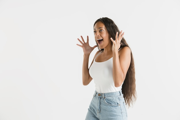 白いスタジオの背景に分離された美しい女性の半分の長さの肖像画。長い髪の若い感情的なアフリカ系アメリカ人の女性。顔の表情、人間の感情の概念。びっくり、興奮。