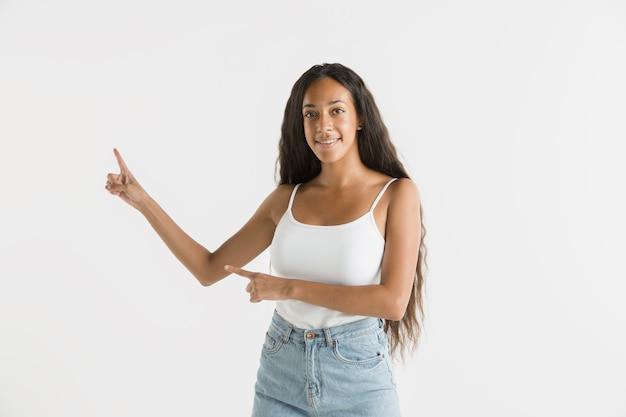 白いスタジオの背景に分離された美しい女性の半分の長さの肖像画。長い髪の若い感情的なアフリカ系アメリカ人の女性。顔の表情、人間の感情の概念。空のスペースバーを表示しています。