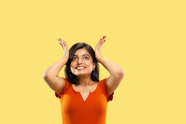 노란색 공간에 고립 된 아름 다운 여성 절반 길이 초상화. 드레스에 젊은 감정적 인 인도 여자는 경악하고 행복합니다. 부정적인 공간