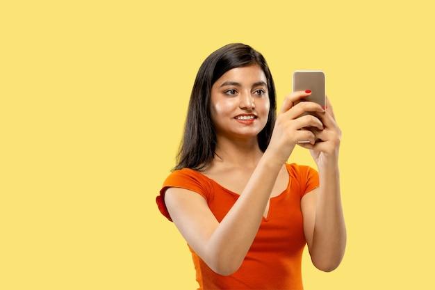 黄色の空間に分離された美しい女性の半分の長さの肖像画。自撮りを作るドレスを着た若い感情的なインドの女性。ネガティブスペース