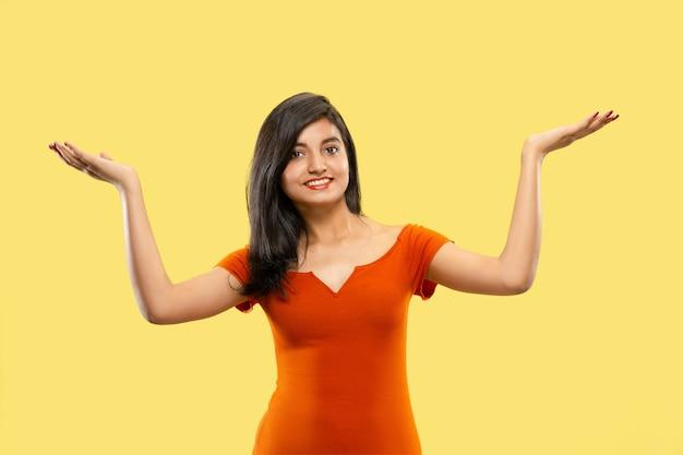 노란색 공간에 고립 된 아름 다운 여성 절반 길이 초상화. 드레스 가리키고 보여주는 젊은 감정적 인 인도 여자. 부정적인 공간