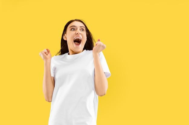 노란색 공간에 고립 된 아름 다운 여성 절반 길이 초상화. 젊은 웃는 여자. 표정, 여름, 주말, 리조트 컨셉