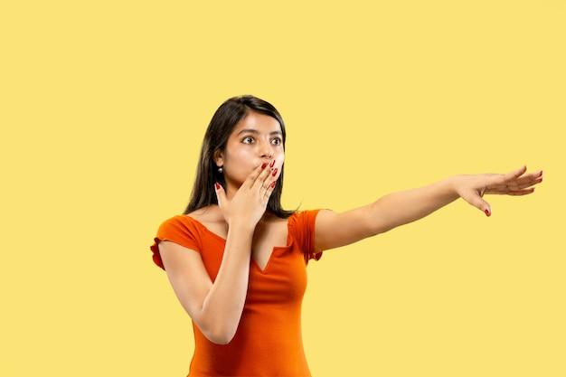 Красивый женский поясной портрет, изолированные на желтом фоне студии. молодая эмоциональная индийская женщина в платье указывая и показывая. негативное пространство. выражение лица, концепция человеческих эмоций.