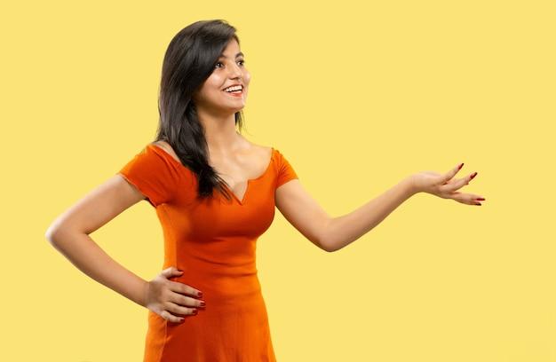 黄色で隔離の美しい女性の半分の長さの肖像画