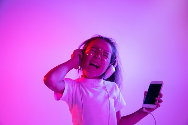 Beautiful female half-length portrait isolated on purple backgroud in neon light. emotional girl in eyeglasses. human emotions, facial expression concept. dancing, listening to music, making selfie.