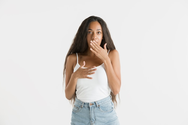 Beautiful female half-length portrait isolated on white studio background. young emotional african-american woman with long hair. facial expression, human emotions concept. astonished, excited.