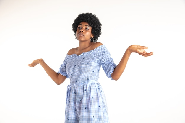 Beautiful female half-length portrait isolated on white  wall. young emotional african-american woman in blue dress. facial expression, human emotions concept. unknowing, uncertainty.