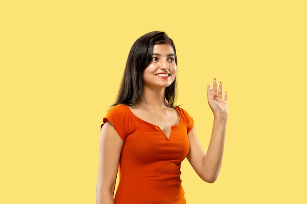 Beautiful female half-length portrait isolated on yellow  space. young emotional indian woman in dress greeting and inviting. negative space